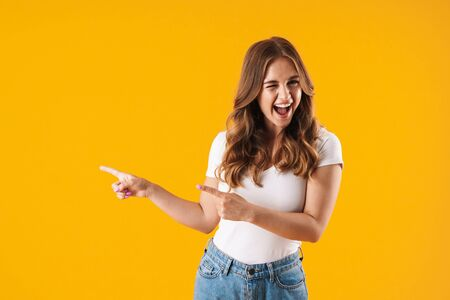 Excited young girl wearing casual clothes standing isolated over yellow background, pointing away at copy space