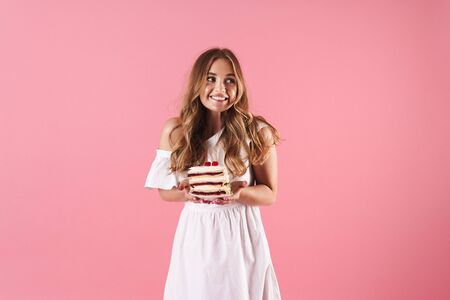 Image of happy confused woman wearing white dress looking aside and holding piece of cake isolated over pink background Stock Photo