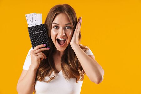 Photo of gorgeous young woman rejoicing while holding passport and travel tickets isolated over yellow background Imagens