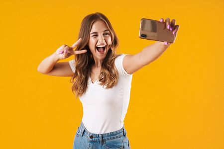 Portrait of a cheerful young casual girl standing isolated over yellow background, taking a selfie, peace gesture