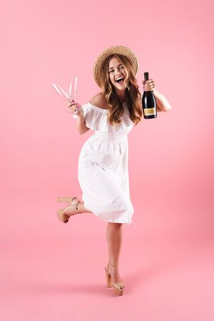 Beautiful excited young blonde girl wearing summer dress standing isolated over pink background, celebrating with bottle of champagne and two glasses Imagens