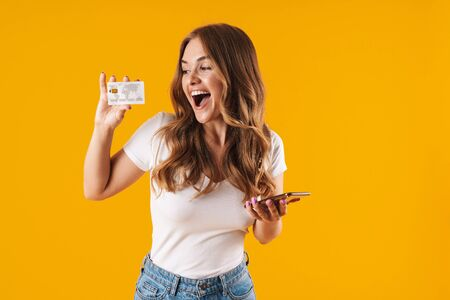 Photo of beautiful young woman rejoicing while holding credit card and smartphone isolated over yellow background