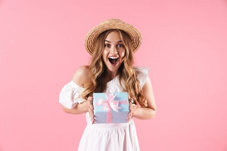 Image of caucasian delighted woman wearing straw hat wondering and holding present box isolated over pink background
