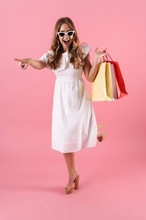 Image of excited young woman wearing sunglasses pointing finger aside and holding shopping bags isolated over pink background