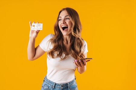 Photo of delighted young woman rejoicing while holding credit card and smartphone isolated over yellow background