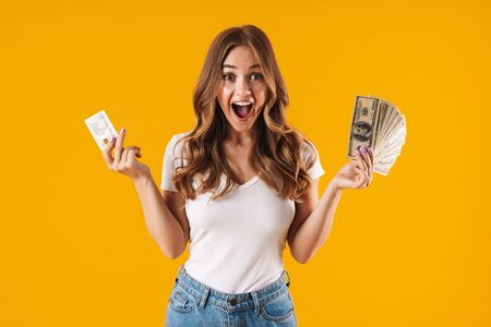 Photo of caucasian delighted woman rejoicing while holding fan of dollar money and credit card isolated over yellow background Imagens