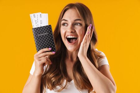 Photo of astonished young woman rejoicing while holding passport and travel tickets isolated over yellow background Imagens