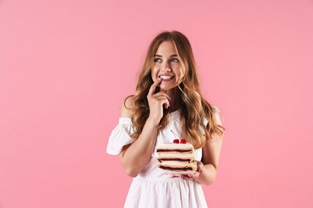Image of happy thinking woman wearing white dress looking upward with her finger on her teethes and holding piece of cake isolated over pink background Stock Photo