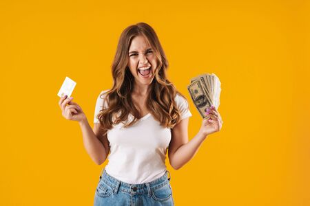 Photo of amazed delighted woman rejoicing while holding fan of dollar money and credit card isolated over yellow background Imagens