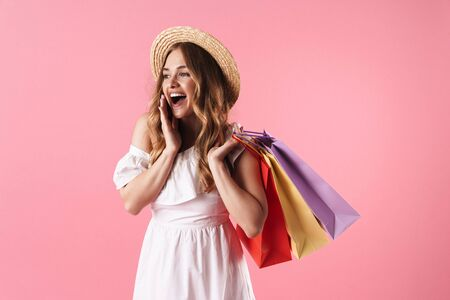 Image of beautiful amazed woman wearing straw hat wondering and holding shopping bags isolated over pink background