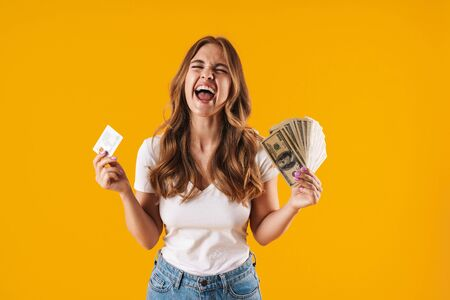 Photo of ecstatic delighted woman rejoicing while holding fan of dollar money and credit card isolated over yellow background Imagens