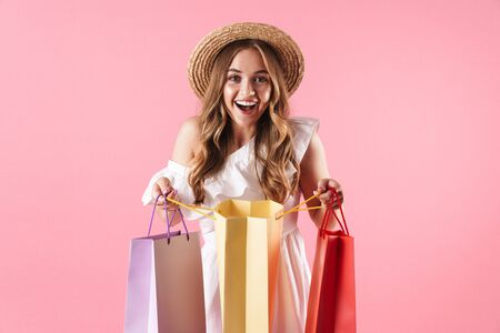 Image of caucasian amazed woman wearing straw hat wondering and holding shopping bags isolated over pink background