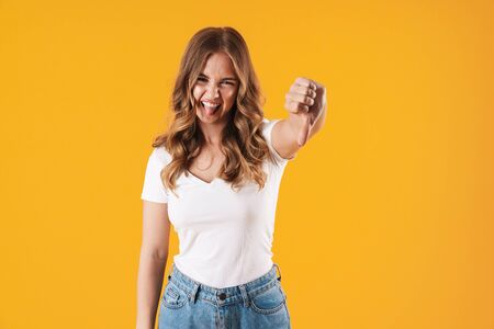 Image closeup of playful caucasian woman wearing basic t-shirt sticking out her tongue and showing thumb down isolated over yellow wall Фото со стока