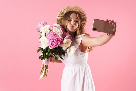 Image of blond happy woman wearing straw hat making kiss and taking selfie photo on cellphone with flowers isolated over pink background