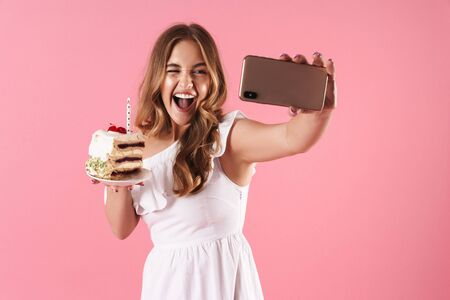 Image of young laughing woman taking selfie photo on cellphone and winking while holding piece of cake with candle isolated over pink background