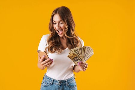 Portrait of a cheerful young casual girl standing isolated over yellow background, showing money banknotes while using mobile phone 스톡 콘텐츠