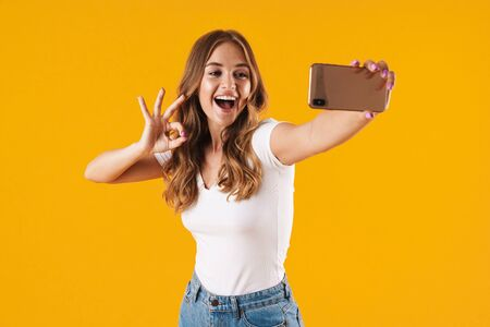 Portrait of a cheerful young casual girl standing isolated over yellow background, taking a selfie, showing ok