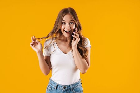 Excited young girl wearing casual clothes standing isolated over yellow background, talking on mobile phone