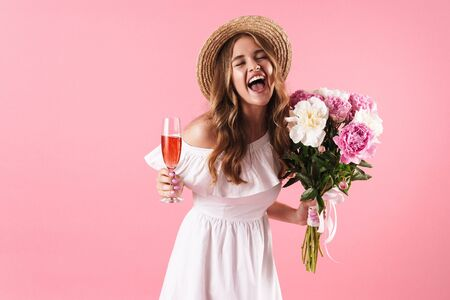 Image of blond cheerful woman wearing straw hat laughing while holding flowers and glass of champagne isolated over pink background