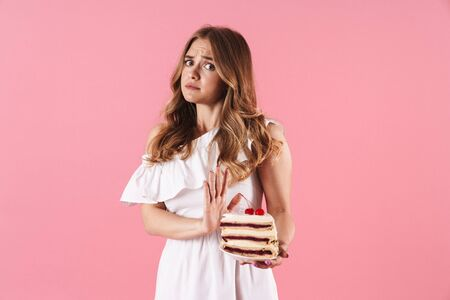 Image of young confused woman wearing white dress doing stop gesture and holding piece of cake isolated over pink background 스톡 콘텐츠