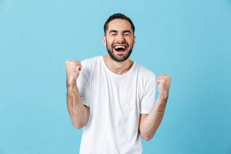Image of excited young screaming happy bearded man posing isolated over blue wall background make winner gesture.