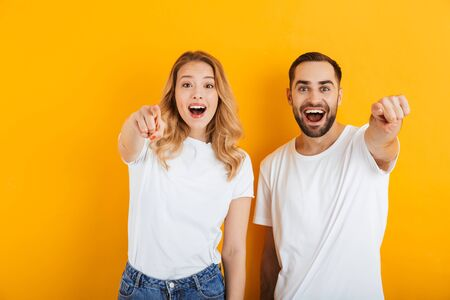 Portrait of happy young couple man and woman in basic t-shirts smiling and pointing fingers at camera isolated over yellow background
