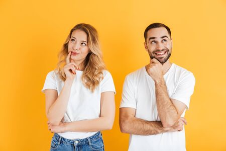 Image of thoughtful couple man and woman dreaming and thinking while looking upward together isolated over yellow background 免版税图像