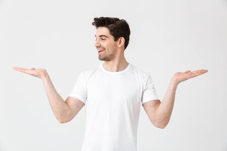 Portrait of a cheerful young man wearing casual clothing isolated over white background, presenting copy space