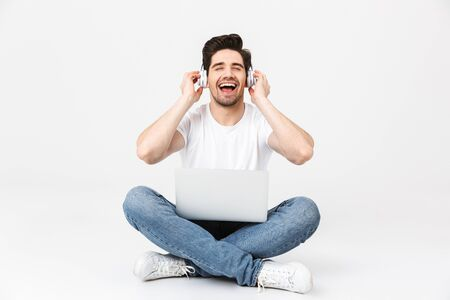 Full length portrait of a cheerful young man wearing casual clothing isolated over white background, sitting with laptop computer, wearing headphones 스톡 콘텐츠