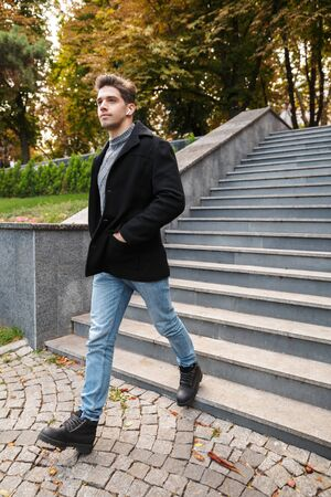 Photo of young serious man in casual clothing walking outdoors in green park by steps listening music with earphones.