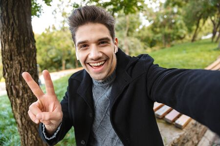 Image of cheerful young man in casual clothing walking outdoors in green park take a selfie by camera listening music with earphones showing peace gesture.
