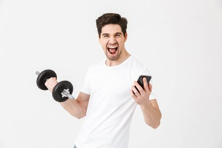 Image of emotional happy excited young man posing isolated over white wall holding dumbbell make exercise using mobile phone. Фото со стока