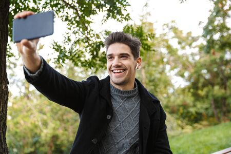 Image of cheerful young man in casual clothing walking outdoors in green park using mobile phone take a selfie.