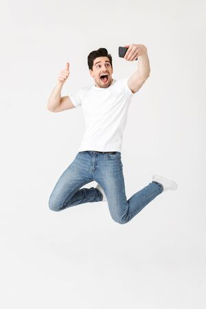 Image of excited happy young man posing isolated over white wall background using mobile phone take a selfie make a thumbs up gesture. Imagens