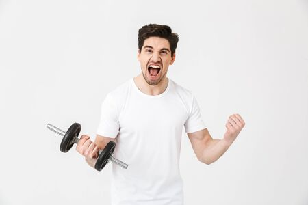 Image of emotional screaming excited young man posing isolated over white wall holding dumbbell make exercise.