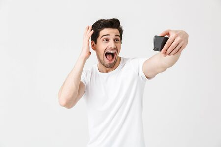Image of happy emotional young man posing isolated over white wall background take selfie by mobile phone.