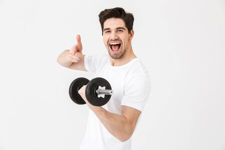 Image of emotional happy excited young man posing isolated over white wall holding dumbbell make exercise pointing.