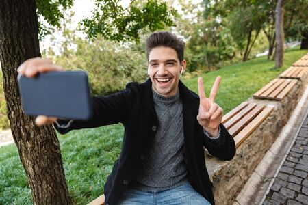 Picture of a cheerful pleased young man in casual clothing walking outdoors in green park using mobile phone take a selfie with peace gesture.