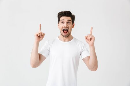 Portrait of a cheerful young man wearing casual clothing isolated over white background, presenting copy space Stock Photo