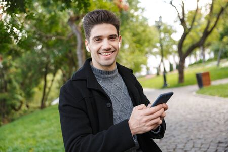 Image of a pleased young cheerful man in casual clothing walking outdoors in green park using mobile phone listening music with earphones.