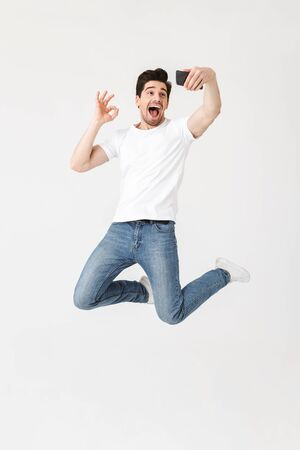 Image of excited happy young man posing isolated over white wall background using mobile phone take a selfie showing okay gesture.