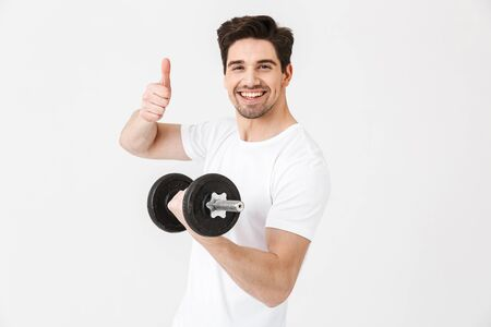 Image of emotional happy excited young man posing isolated over white wall holding dumbbell make exercise make thumbs up gesture. Фото со стока