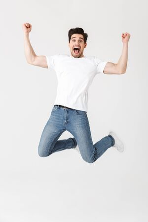 Full length portrait of a cheerful young man wearing casual clothing isolated over white background, jumping Stok Fotoğraf