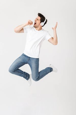 Image of emotional excited young man posing isolated over white wall background listening music with headphones singing jumping. 스톡 콘텐츠