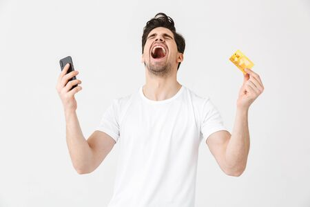 Image of excited emotional screaming happy young man posing isolated over white wall background using mobile phone holding credit card.