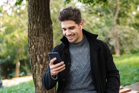 Image of a smiling handsome young cheerful man in casual clothing walking outdoors in green park using mobile phone listening music with earphones.