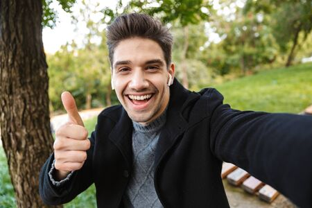 Image of pleased happy young man in casual clothing walking outdoors in green park take a selfie by camera listening music with earphones showing thumbs up gesture. 스톡 콘텐츠
