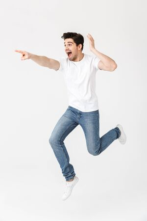 Full length portrait of a cheerful young man wearing casual clothing isolated over white background, presenting copy space, jumping