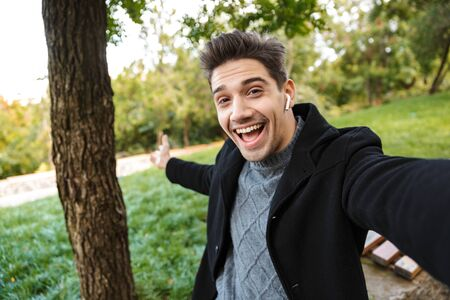 Image of optimistic pleased young man in casual clothing walking outdoors in green park take a selfie by camera listening music with earphones showing copyspace.