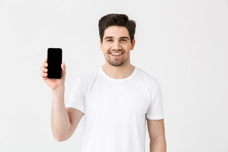 Portrait of a cheerful young man wearing casual clothing isolated over white background, showing blank screen mobile phone Imagens